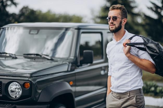 Hombre viajando con bolsa y de pie junto al coche.