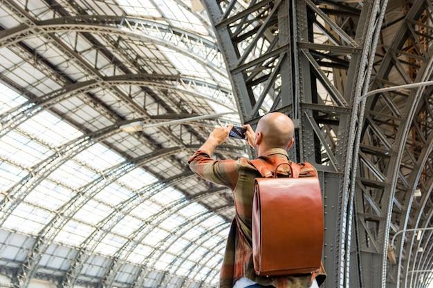 Hombre viajando con mochila tomando fotos
