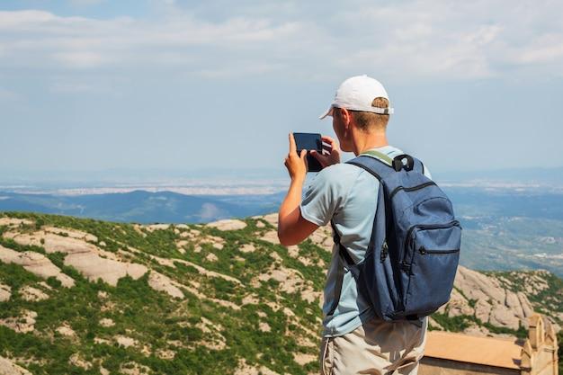 Hombre de viaje con mochila de pie, tome una foto con el teléfono inteligente mountians sunny day copie el espacio