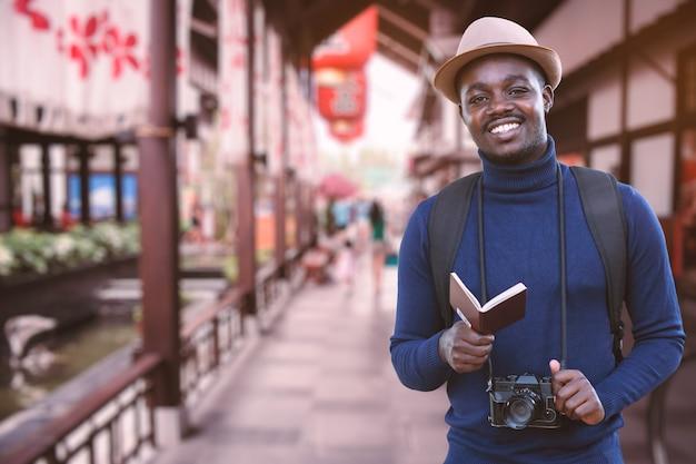 Hombre viajero africano viaja en asia con pasaporte y cámara vintage