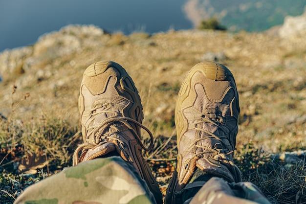 Hombre viajero en botas de montaña se sienta en la parte superior