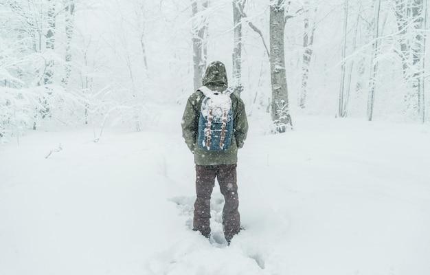 Hombre viajero caminando en bosque nevado