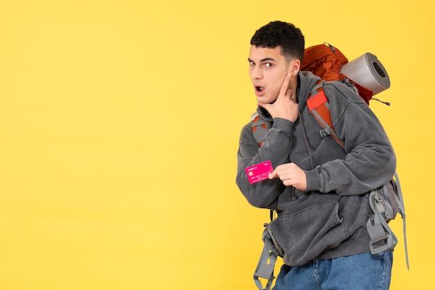 Hombre viajero divertido vista frontal con mochila roja con tarjeta de descuento