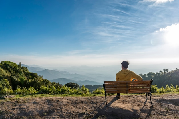 Hombre viajero emplazamiento banco de madera con fondo de montañas, doi inthanon tailandia,