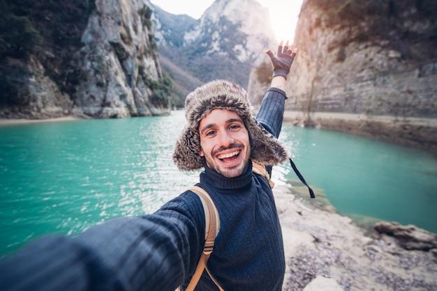 Hombre viajero feliz toma una foto selfie en un lago en la montaña