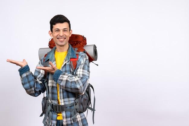 Hombre viajero feliz vista frontal con mochila apuntando a algo
