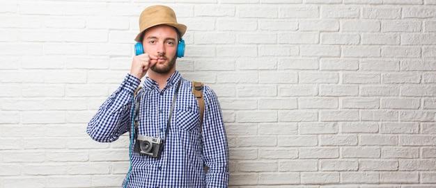Hombre viajero joven con mochila y una cámara vintage que guarda un secreto o pide silencio.