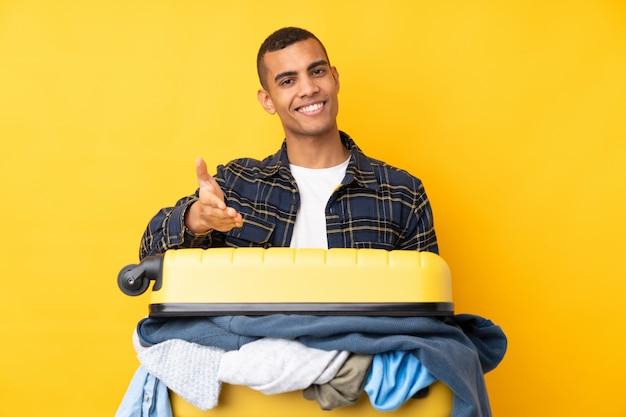 Hombre viajero con una maleta llena de ropa sobre la pared amarilla aislada apretón de manos después de un buen trato