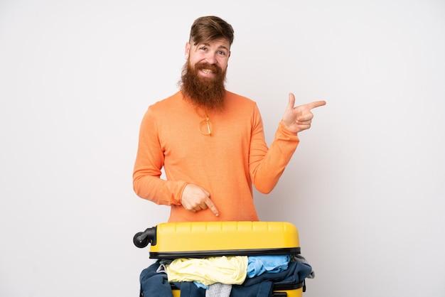 Hombre viajero con una maleta llena de ropa sobre la pared blanca aislada que señala el dedo hacia un lado