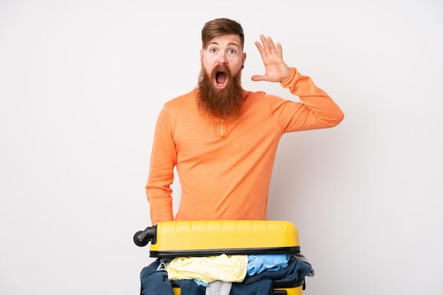 Hombre viajero con una maleta llena de ropa sobre pared blanca aislada sorprendido y apuntando con el dedo hacia un lado