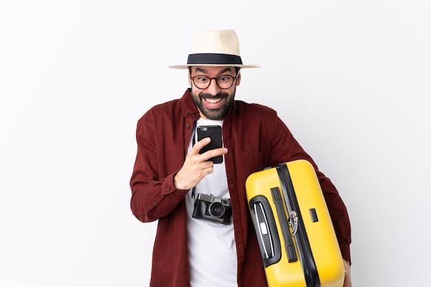 Hombre viajero con maleta sobre pared aislada