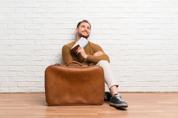 Hombre viajero con maleta y tarjeta de embarque mirando hacia arriba mientras sonríe