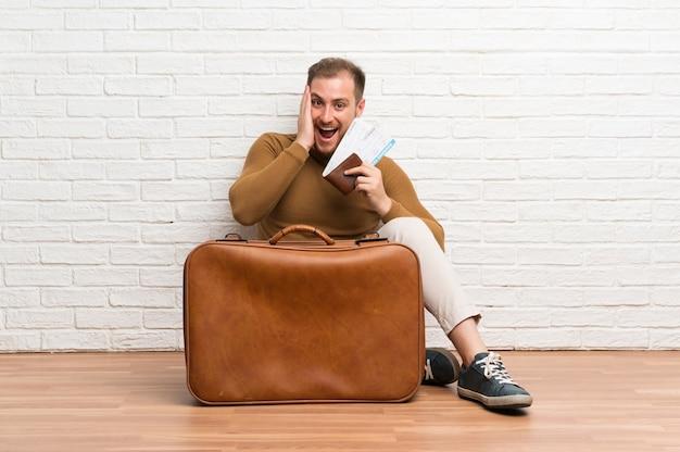 Hombre viajero con maleta y tarjeta de embarque con sorpresa y expresión facial conmocionada
