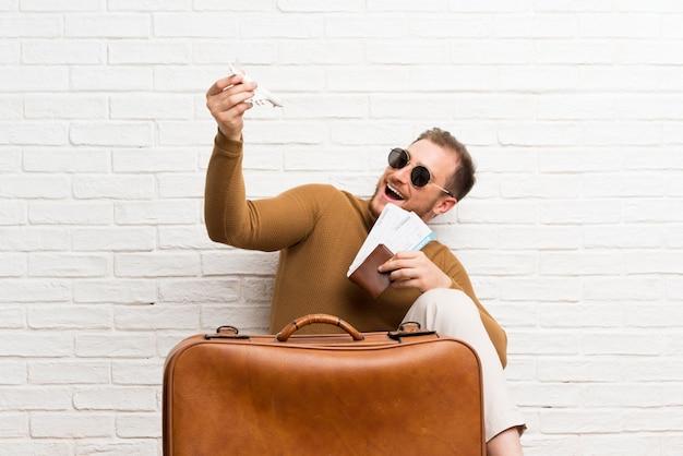Hombre viajero con maleta y tarjeta de embarque y sosteniendo un avión de juguete