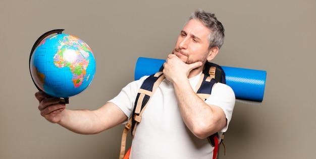 Hombre viajero de mediana edad con un mapa del mundo