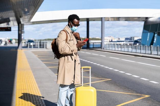 Hombre viajero milenario afroamericano con maleta se encuentra en la terminal del aeropuerto
