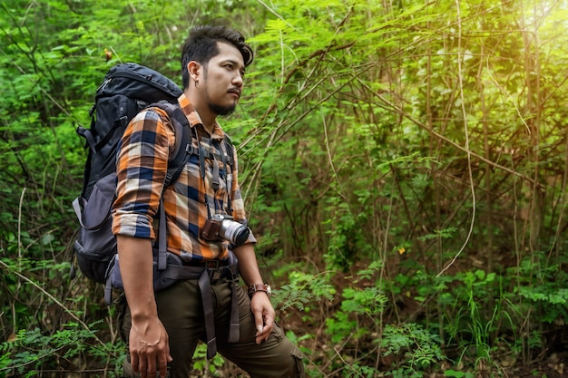 Hombre viajero con mochila en el bosque
