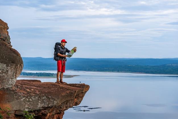Hombre viajero con mochila mirando el mapa en el borde del acantilado, en la cima de la montaña rocosa