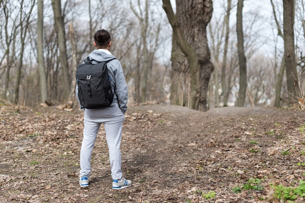 Hombre viajero con mochila de senderismo en el bosque de la primavera, descansando en la cima de la colina. viajes y deporte concepto de estilo de vida. vacaciones extremas al aire libre.