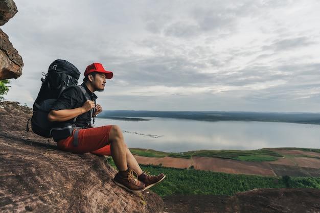 Hombre viajero con mochila sentado en el borde del acantilado, en la cima de la montaña rocosa