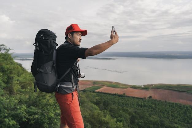 Hombre viajero con mochila con teléfono inteligente tome una selfie en el borde del acantilado, en la cima de la montaña rocosa