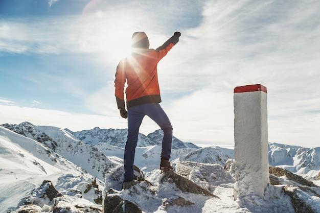 Hombre viajero en las montañas con la mano levantada mientras el ganador se para arriba.