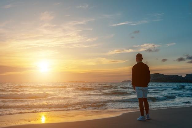 Hombre viajero en una playa tropical durante el atardecer. vacaciones de vacaciones y concepto de viaje.