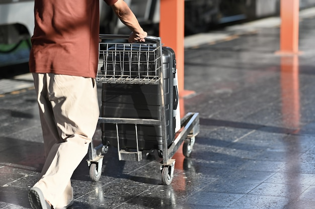 Hombre del viajero que sostiene un carro con el bolso en la estación de tren.