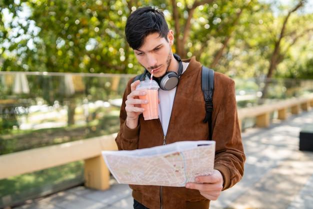 Hombre viajero sosteniendo un mapa y buscando direcciones