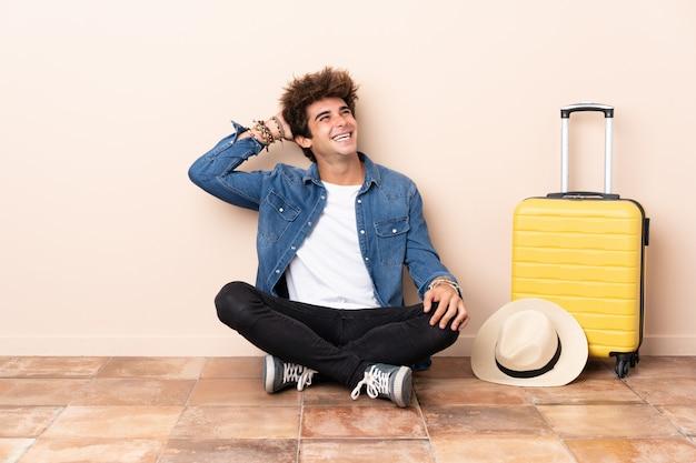 Hombre viajero su maleta sentada en el suelo riendo
