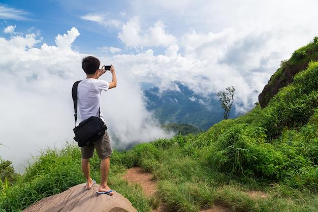 Hombre viajero toma foto vista a la montaña con teléfono móvil.