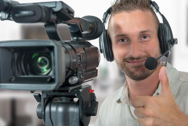 Hombre con videocámara profesional y auriculares.