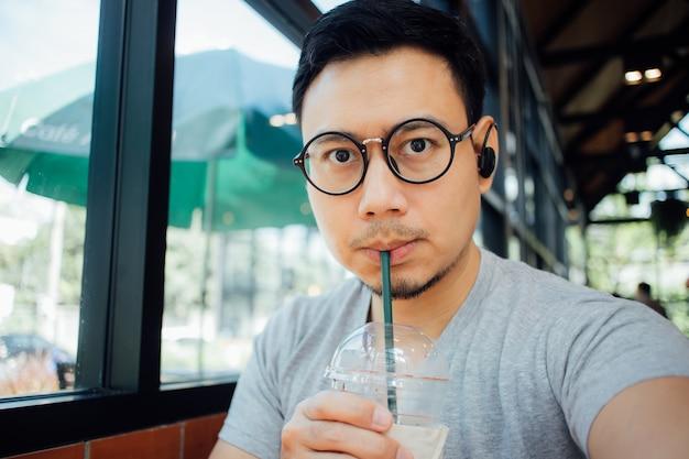 El hombre con los vidrios selfy sí mismo bebe el café en el café.