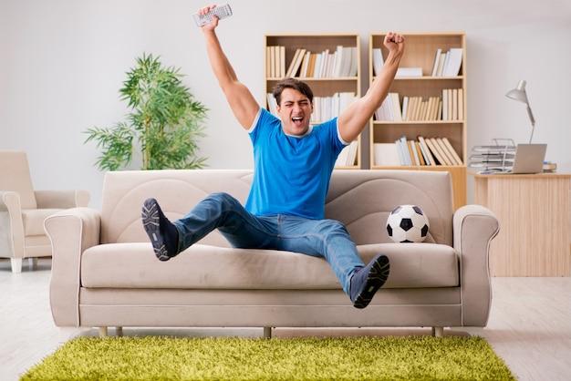 Hombre viendo futbol en casa
