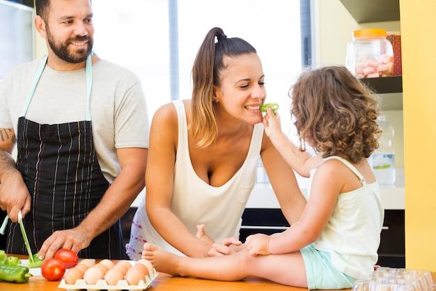 Hombre viendo niña alimentar con pimiento a su madre