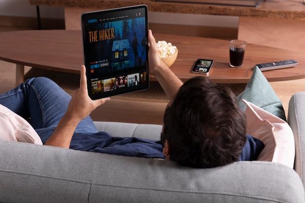 Hombre viendo su película favorita en una tableta