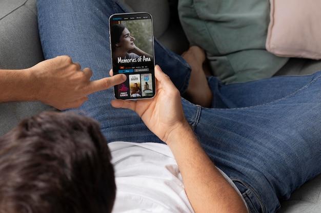 Hombre viendo su película favorita en un teléfono inteligente