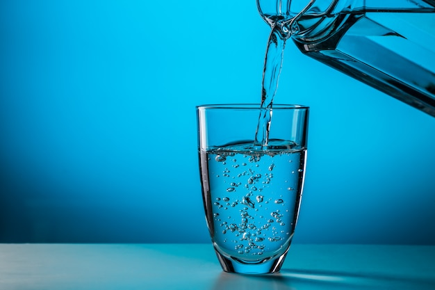 Hombre vierte agua de vidrio