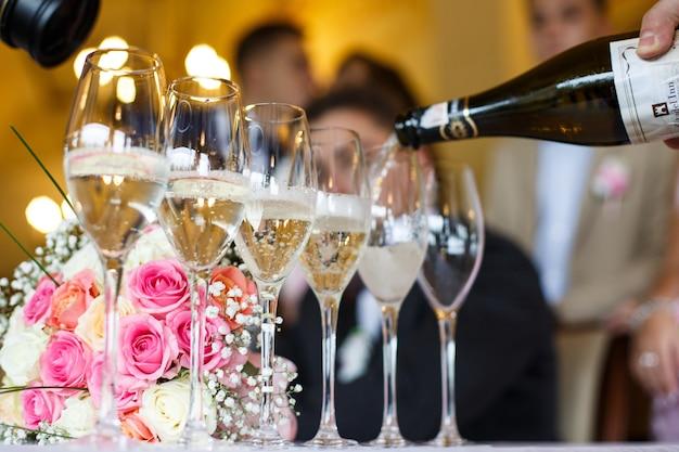 El hombre vierte champán en los vasos