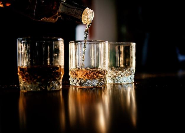 El hombre vierte whisky en las copas de pie delante de una mesa de madera