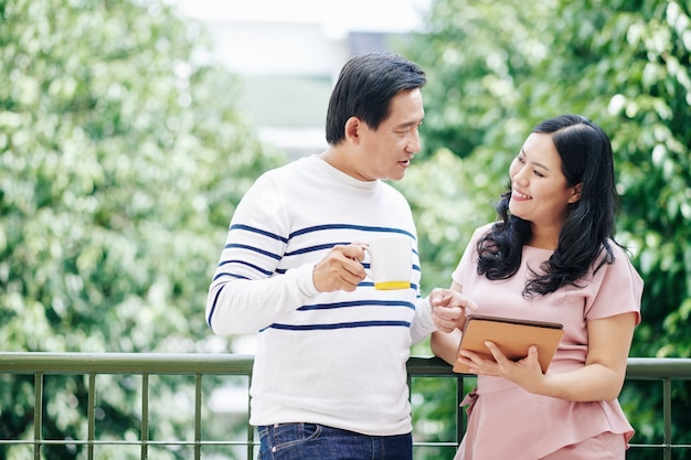 Hombre vietnamita maduro bebiendo una taza de café por la mañana y hablando con su esposa sonriente con una computadora de mesa en las manos