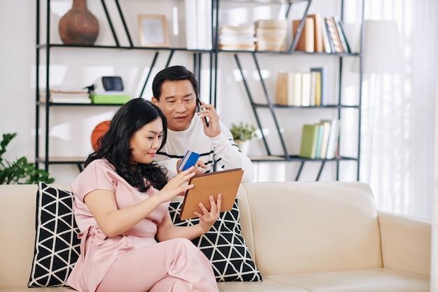 Hombre vietnamita maduro hablando por teléfono con el gerente de la tienda online al pedir el artículo en la pantalla de la tableta en manos de su wofe