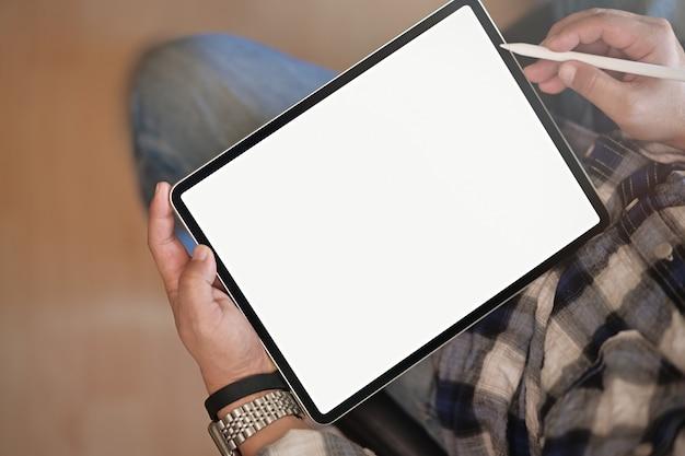 Hombre de la visión superior en los vaqueros que se sientan en casa y que sostienen la tableta