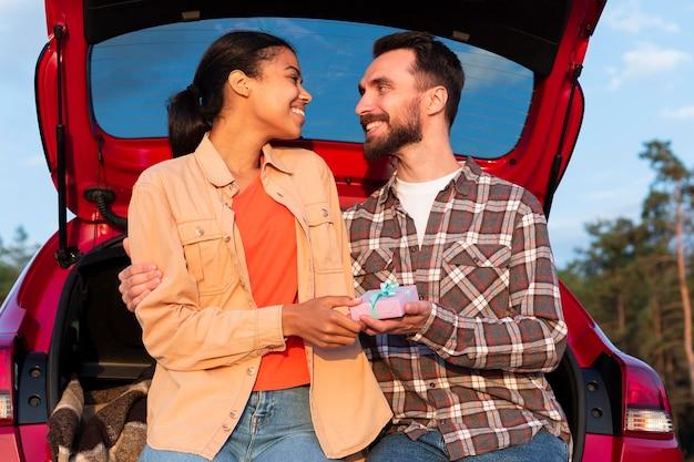 Hombre de vista frontal dando un regalo a su novia