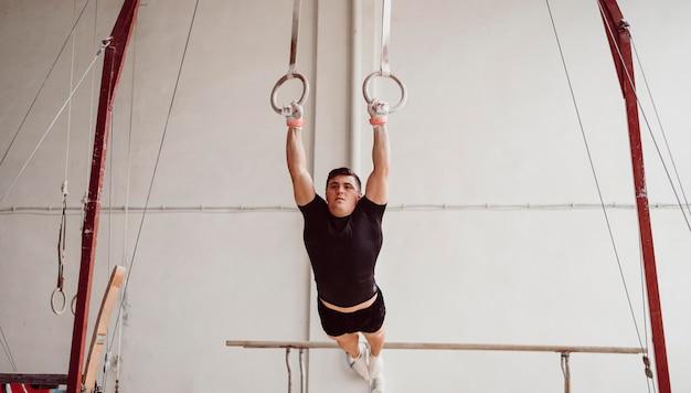 Hombre de vista frontal entrenando en anillos de gimnasia