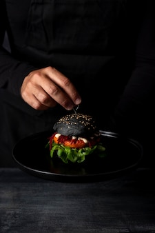 Hombre de vista frontal poniendo brocheta en hamburguesa