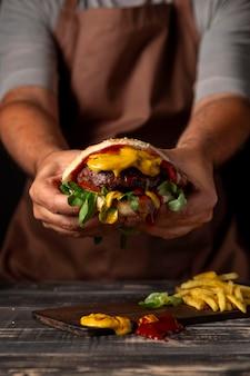 Hombre de vista frontal sosteniendo hamburguesa