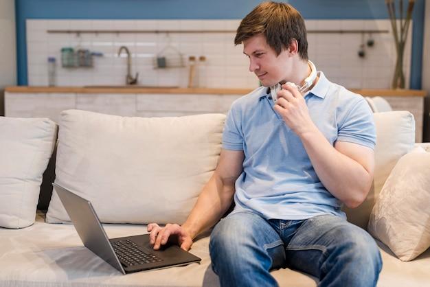 Hombre de vista frontal trabajando en la computadora portátil desde casa