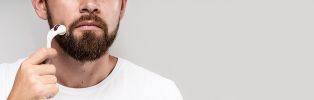 Hombre de vista frontal usando un rodillo facial con espacio de copia