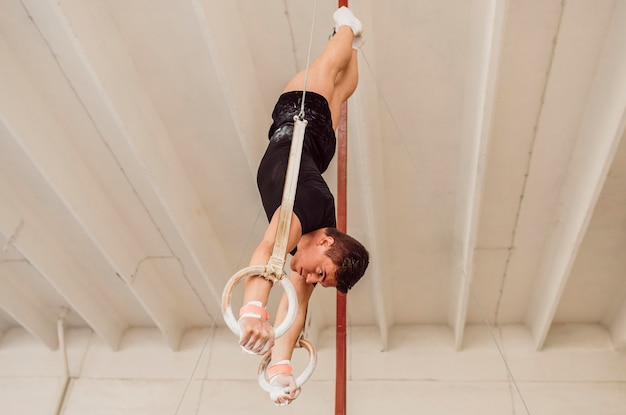 Hombre de vista lateral entrenando en anillos de gimnasia
